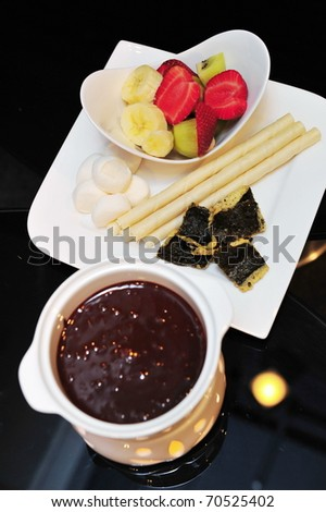 Set of dark chocolate fondue with dipping ingredients