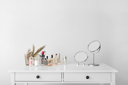 Set of decorative cosmetics and mirrors on dressing table