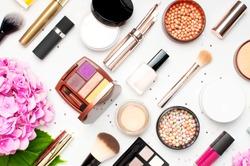 Set of decorative cosmetics mascara powder lipstick eyeshadow blush makeup brush pink hydrangea flowers star confetti on light background top view Flat lay. Beauty blogger concept. Fashion background