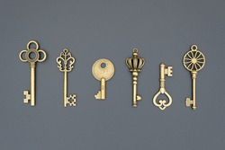 set of decorative gilded and aged keys made of copper or bronze, close-up, top view, flat lay, isolated on black background, group of plated vintage objects for decoration and design