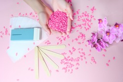 Set of depilation and beauty on pink background concept - sugar paste or hair removal waxing melted paste and stripes, orchid and female hands. Film Wax Granules or hot wax, cartridge, wooden spatula