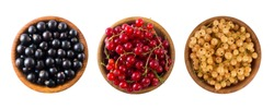 Set of different color currants isolated on white background cut out. White, red and black currant in a wooden bowl with copy space for text. Top view. Currants isolated on white background. Berries.