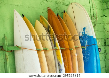 Set of different color surf boards in a stack by ocean.Bali,Indonesia. Surf boards on sandy Weligama beach. On Weligama beach surf is available all year around for beginner and advanced.