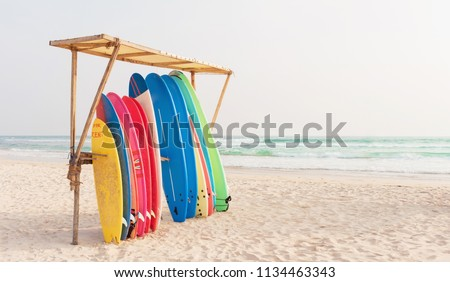 Set of different color surf boards in a stack by ocean. Weligama, SRI LANKA. Surf boards for rent on sandy beach. Soft toned photo. #1134463343