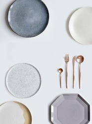 Set of different colorful dishes. Tableware and decorations for serving a festive table. Modern Plates and cutlery copper color. Top view. Isolated background.