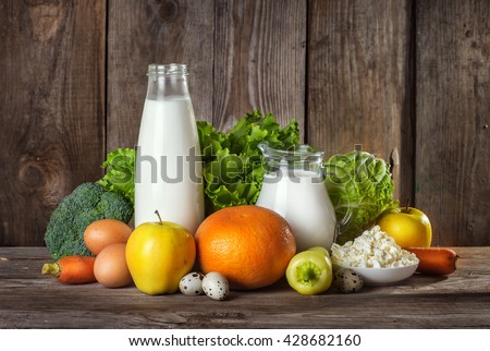 Set of different foods on the old wooden background, vegetables, fruit, eggs, dairy products, the concept of a balanced diet, vegetarian food