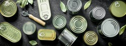 Set of different kinds of tin cans with canned food. On black rustic background