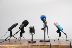Set of different microphones on wooden table. Journalist's equipment