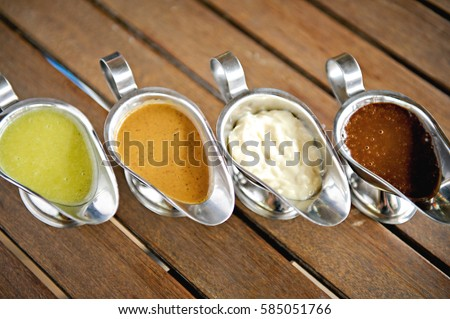 Set of different sauces in stainless steel gravy boats on the wooden table Сток-фото ©