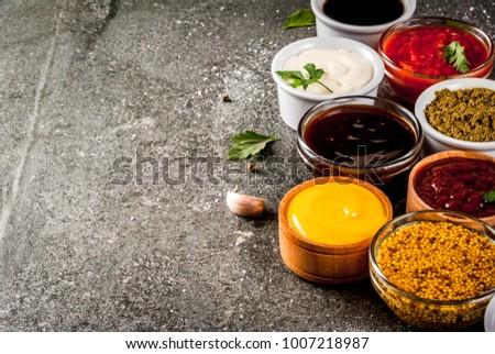 Set of different sauces - ketchup, mayonnaise, barbecue, soy, teriyaki, mustard, grain hills, pesto, adzhika, chutney, tkemali, pomegranate sauce on black stone background. Copy space