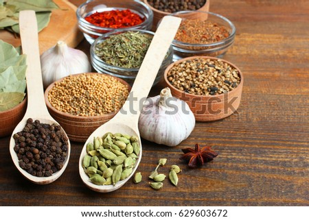 Set of different spices on a wooden background #629603672