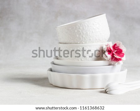 Set of different white ceramic dishes on a light grey background. Elegant white tableware. Minimalistic still life. Soft light, high key.