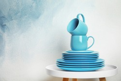 Set of dinnerware on table against light background with space for text. Interior element