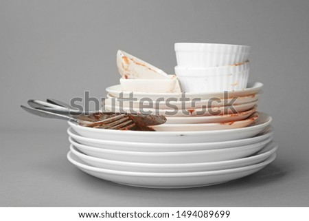 Set of dirty dishes on grey background