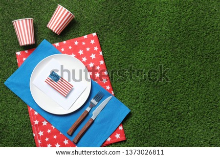 Set of dishware on green grass, top view with space for text. USA Independence Day