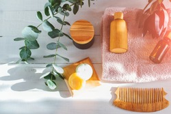 Set of Eco cosmetics products and tools. Soap, shampoo, galss, wood bottles, eucalyptus branch, wooden hair comb, handmade soap, sun glare. Zero waste, Plastic free. Sustainable lifestyle concept.