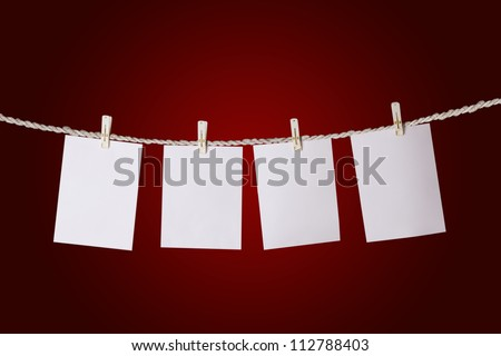 Set of empty paper with copy space  tags hanging on the rope over on red background