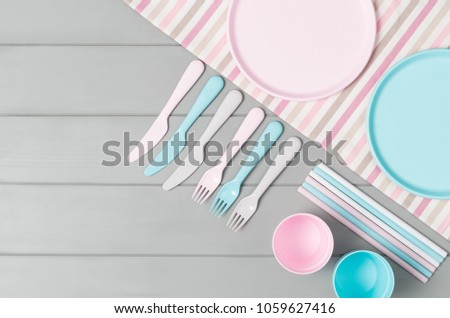 Set of empty, pastel plastic tableware bowls, spoons, knifes and forks isolated on gray wooden background. Flat lay, top view with minimal style. #1059627416