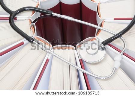 Set of encyclopedias, books and stethoscope closeup.