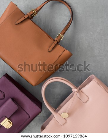 set of fashionable women's handbags on grey plastered surface, top view