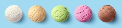 Set of five various ice cream scoops or balls on blue background. Top view. Vanilla, strawberry, caramel, pistachio and chocolate flavor