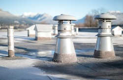 Set of flat roof vents on building with modified bitumen roofing system. Group of different shaped metal ventilators such as: bathrooms and laundry exhaust and plumbing stack vent. Selective focus.