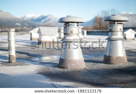 Set of flat roof vents on building with modified bitumen roofing system. Group of different shaped metal ventilators such as: bathrooms and laundry exhaust and plumbing stack vent. Selective focus. stock photo