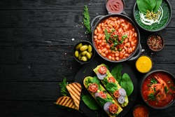 Set of food on black stone background. Dishes of beans, vegetables and seafood.