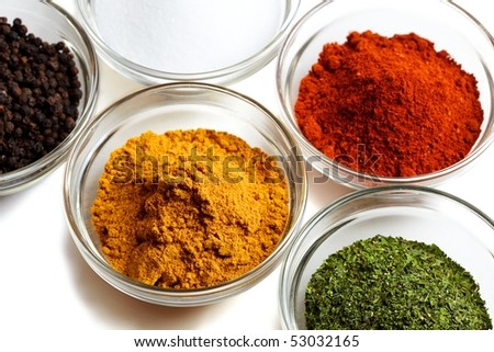 Set of four different coloured spices in glass bowls