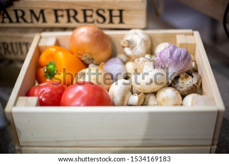 set of fresh organic vegetables garlic, champignons, onion, tomatoes and peppers lie in a light wooden box close-up. Concept of biological, bio products, bio ecology, grown by yourself, vegetarians,  #1534169183