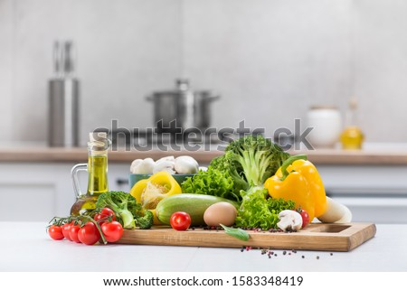 Set of fresh raw vegetables tomato, egg, mushrooms, salad, pepper, squash on a white wood table in a modern kitchen room. Healthy Eating. Organic food.