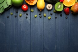 Set of fresh vegetables, fruits and berries on wooden background