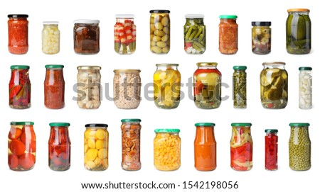 Set of glass jars with different pickled vegetables on white background Foto d'archivio ©