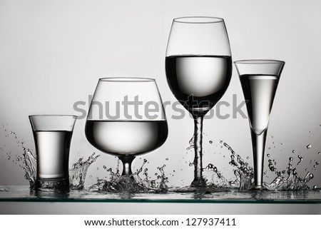 Set of glasses for alcoholic drinks with water splash