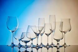 Set of glasses for different alcoholic drinks and cocktails  on light blue-yellow background. Empty clear glassware.