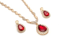 set of gold earrings and a necklace with a ruby isolated on white