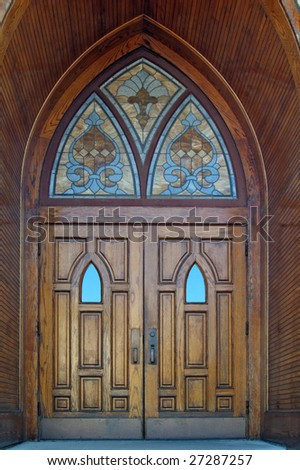 Set of gothic wooden church doors with stained glass windows