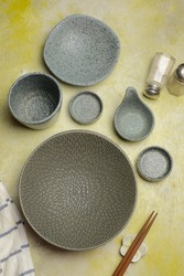 Set of greyish stone ware, Empty grainy stone tableware on yellow rustic table. Top view of Handmade pottery, plates,glass and  wood chopsticks with white blie stripe napkin