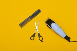 Set of hairdresser (barber) on a yellow background. Hair clipper, scissors and comb. Top view. Flat lay