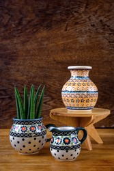 Set of hand made and painted porcelain tableware made in Poland. Bolesławiec pottery on wooden rustic background. Polish craft, culture and pottery