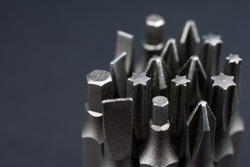 Set of heads for screwdriver (bits) Tools collection copy space, close up, selective focus. blurred dark background