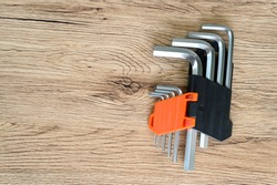 Set of hexagonal keys and screw on a wooden background. Knolling style shot.