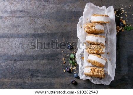 Set of homemade ice cream sandwiches in oat cookies with almond sugar crumbs, blueberries and mint on baking paper over dark metal texture background. Top view with space