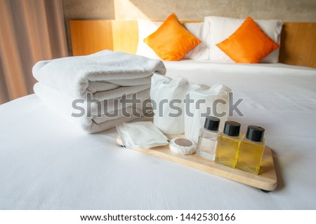 Set of hotel amenities (such as towels, shampoo, soap, drinking glass etc) on the bed. Hotel amenities is something of a premium nature provided in addition to the room when renting a room.