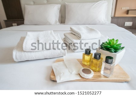 Set of hotel amenities (such as towels, shampoo, soap, gel etc) on the bed. Hotel amenities is something of a premium nature provided in addition to the room when renting a room.