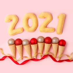Set of ice Cream Cones with Christmas Decoration and number of year 2021, Christmas New Year Concept, pink pastel background, winter holiday flyer, coupon, card