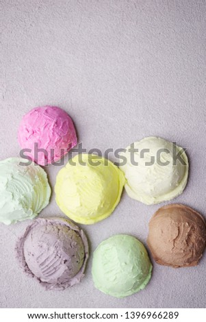 Set of ice cream scoops of different colors and flavors  on stone table, copy space. Food background, summer refreshing concept, traditional seasonal cold sweets