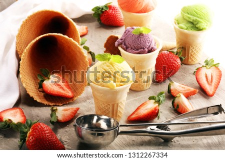 Set of ice cream scoops of different colors and flavors with berries, mint and fruits