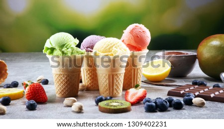 Set of ice cream scoops of different colors and flavors with berries, nuts and fruits and vanilla