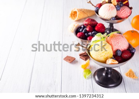 Set of ice cream scoops of different colors and flavours with berries, chocolate on wooden background